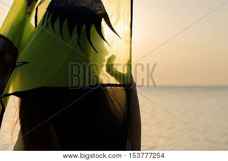 Little girl covers her face with green kite on the beach in the rays of the setting sun