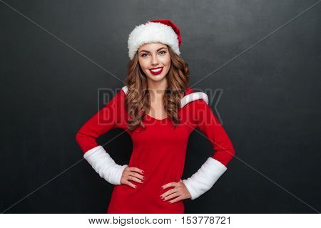 Beautiful woman in santa's costume holding hands on the belt over black background