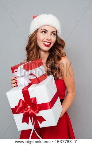 Smiling woman with big and small gifts looking away. Santa's helper. Woman on dress and Santa's hat