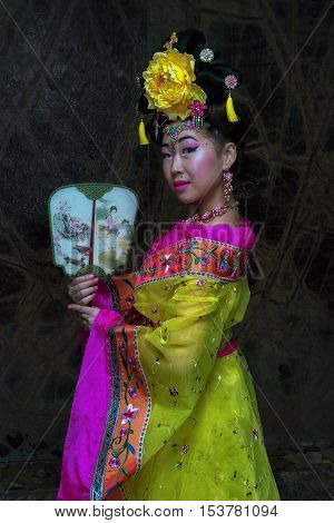 Asian Woman With Chinese Traditional Dress Cheongsam And Holding Chinese Fan. Chinese New Year Conce