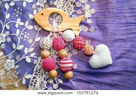 Wooden Fish Toy With Crochet Beads And Heart On A Rug Background