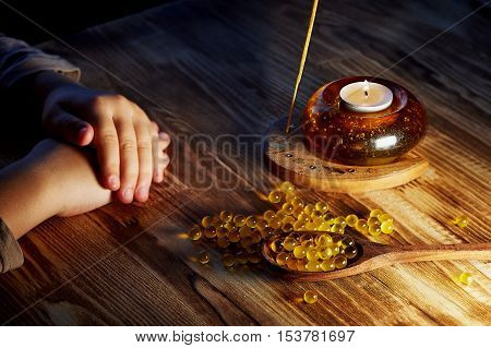 The hands of the child, cod liver oil on a wooden spoon and on a wooden surface is scattered. The candle burns