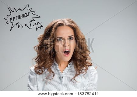 Portrait of young woman with shocked facial expression over gray background with question mark WHAT