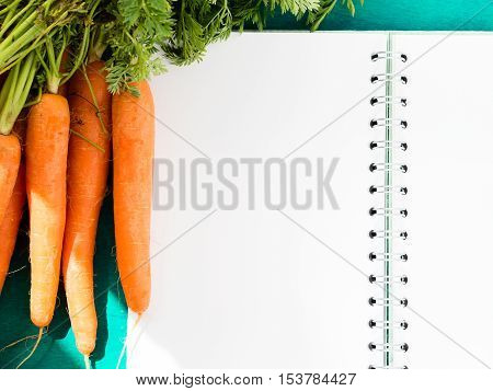 Open paper note book with blank pages on dark green table with carrots