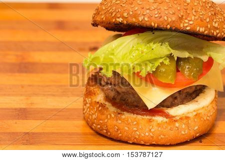 homemade burger with beef cutlet, cucumber, lettuce, onion and yellow cheese on wooden cutting board. closeup shot with negative space