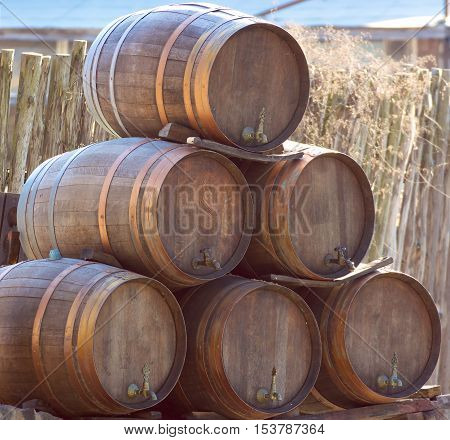 wooden wine barrels kegs stacked in pyramid outside cellar