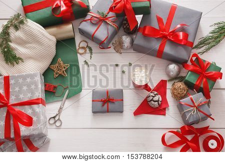 Winter holidays celebrating. Gift wrapping. Packaging modern christmas present boxes in paper with satin red ribbon. Top view on white wood table with fir tree branches, decoration of gift.