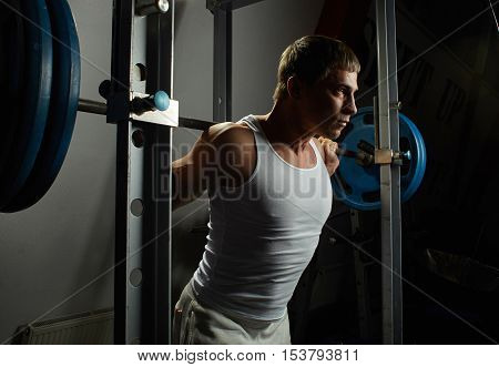 young sportsman put barbell on his shoulder in gym power rack