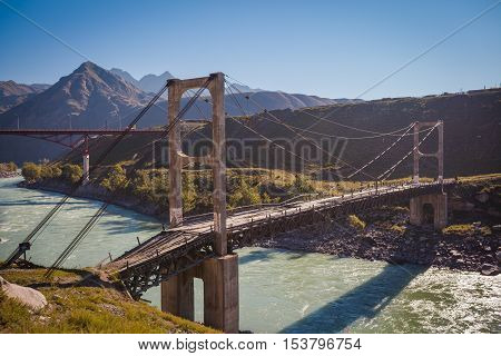The world's first two-chain suspension bridge over the Katun River near Inya Village, the Altai Republic, Russia. Built in 1936. Monument to Russian cultural heritage.