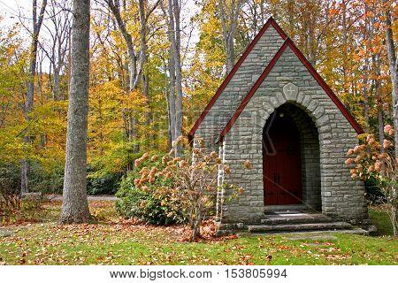 a small stone chapel set amid colorful autumn foliage