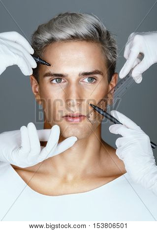 Making improvements. Surgeons draw correction lines on man's face before plastic surgery operation. Beauty concept