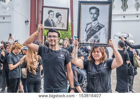Bangkok Thailand - October 22 2016 : Thai people come for singing the anthem and hold the portrait of His Majesty King Bhumibol at the road in front of the Royal Palace to pay respect for the king in Bangkok Thailand.
