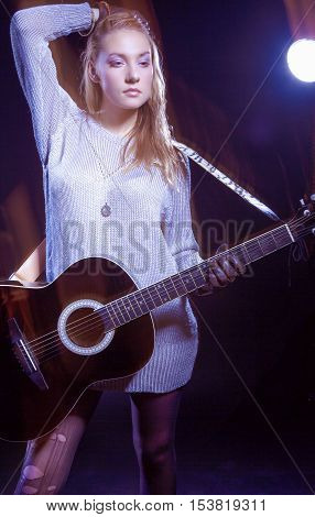 Portrait of Caucasian Expressive Blond Female Posing with Guitar Against Black. Combination of Flash and Halogen Used. Vertical Image Composition