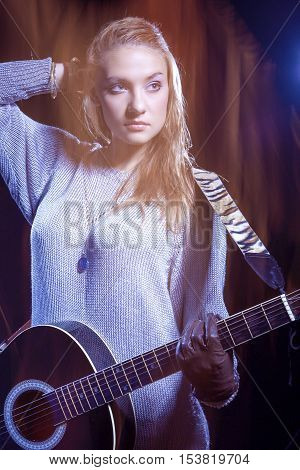 Caucasian Blond Female Musician Posing with Guitar Against Black. Combination of Flash and Halogen Used. Vertical Image