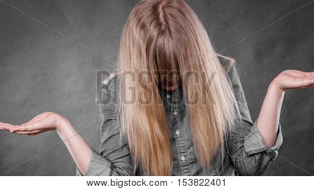Body language. Depression and resignation concept. Young depressed unhappy woman covering facial emotions by blonde hair.