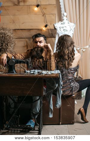 Bearded man tailor or dressmaker and pretty girl customer or sexy model with curly brunette hair and undressed back sit near vintage sewing machine in rustic workshop