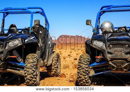 Merzouga Morocco - Feb 21 2016: blue Polaris RZR 800 aligned and stationed with no pilot in Morocco desert near Merzouga. There is a great mountain in the background