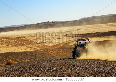 Merzouga Morocco - Feb 25 2016: back view on blue Polaris RZR 800 with it's pilots in Morocco desert near Merzouga. Merzouga is famous for its dunes the highest in Morocco.