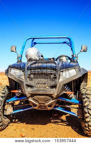 Merzouga Morocco - Feb 21 2016: blue Polaris RZR 800 stationed with no pilot in Morocco desert near Merzouga. Merzouga is famous for its dunes the highest in Morocco.