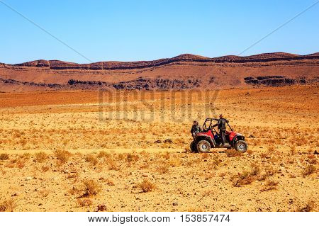 Merzouga Morocco - Feb 21 2016: two pilots women of off-road vehicle RZR waiting assistance in the Moroccan desert near Merzouga. Merzouga is famous for its dunes the highest in Morocco.