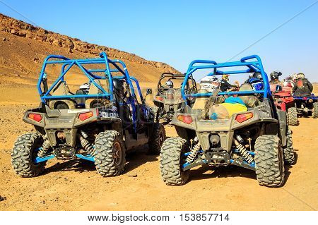 Merzouga Morocco - Feb 24 2016: back view on blue Polaris RZR 800 group of pilots with bickers and quad in Morocco desert near Merzouga. Merzouga is famous for its dunes the highest in Morocco.