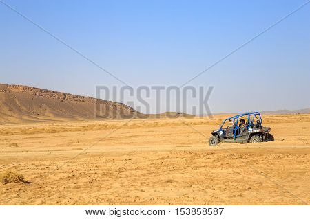 Merzouga Morocco - Feb 24 2016: back view on blue Polaris RZR 800 with it's pilots in Morocco desert near Merzouga. Merzouga is famous for its dunes the highest in Morocco.