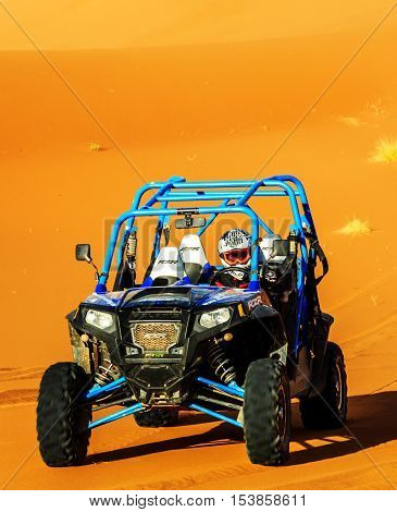 Merzouga Morocco - Feb 22 2016: Front view on blue Polaris RZR 800 with it's pilot in Morocco desert near Merzouga. Merzouga is famous for its dunes the highest in Morocco.