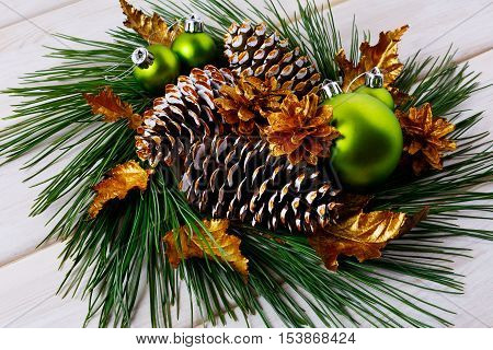Christmas holiday golden cones and leaves decorated wreath. Christmas decoration with golden decor. Christmas table centerpiece.