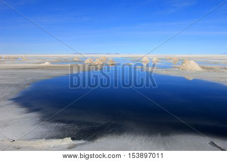 Hills of salt behind lake, salt extraction area at the world's biggest salt lake, Salar de Uyuni, Bolivia