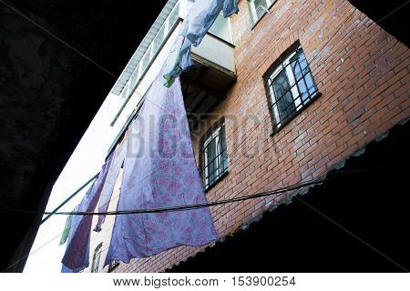 Poor area of the city. Residential and densely populated residential quarter close. Brick wall with bed covers drying outside of the ghetto. A poor hopeless life of poor people in the slums.