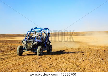 Merzouga Morocco - Feb 25 2016: Front view on blue Polaris RZR 800 with it's pilot in Morocco desert near Merzouga. Merzouga is famous for its dunes the highest in Morocco.