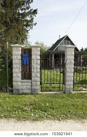House behind the fence with a gate and a blue mailbox
