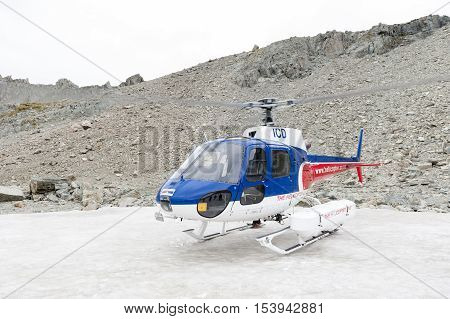 Mount Cook New Zealand - February 2016: Helicopter from The Helicopter Line Company landing on snowcapped mountain peak around Aoraki Mount Cook and Mount Cook National Park.