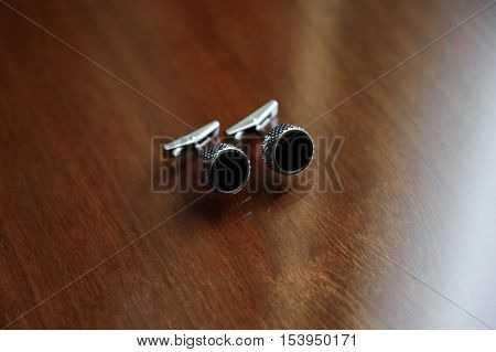 A silver Cufflinks with black inserts on wooden background
