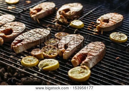 Grilled salmon steak on the flaming. Decorated with Basil and lemon.