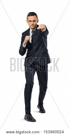 A businessman full-height full-faced, looking directly into the camera in a boxing pose isolated on the white background. Business and management. Poses and gestures. Power and confidence.