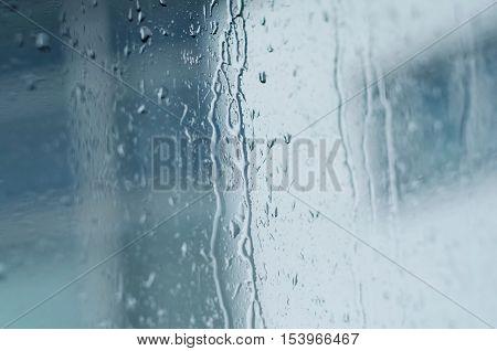 Raindrops on window glass toned blue tilt shift
