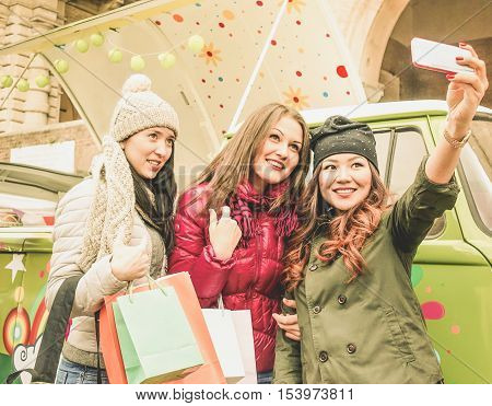 Multiracial friends taking selfie after sopping with minivan in background - Young people having fun together in winter time - Fashion and shopping addiction concept - Main focus on right girl