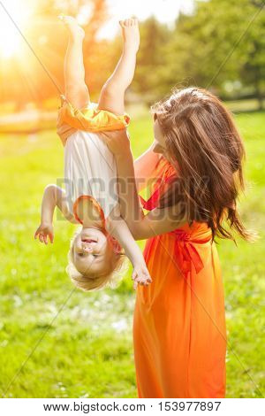 Beautiful Mom and baby outdoors. Happy family playing in nature. Mom and baby. Mother and child.