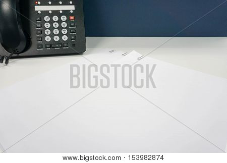 mock up white paper sheet with paper clip in IP phone backdrop