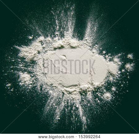 White powder (flour or starch) on a black background.