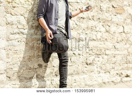 people and technology concept - close up of man with earphones and smartphone listening to music and playing imaginary guitar at brick wall on street