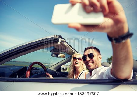 road trip, leisure, couple, technology and people concept - happy man and woman driving in cabriolet car and taking selfie with smartphone