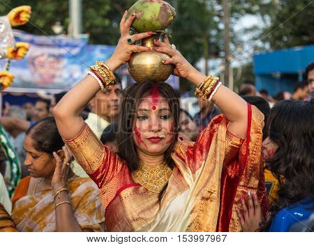 KOLKATA, INDIA - OCTOBER 11, 2016: Hindu married woman holds a pitcher on her head as part of a ritual of Durga Puja immersion ceremony at Babughat Kolkata, West Bengal, India.