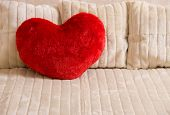 Fluffy soft red heart. Pillow on a bed. poster