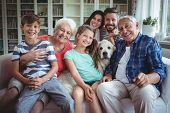 Portrait of happy multi-generation family sitting on sofa in living room at home poster