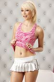 picture of up-skirt  - Cute young blond model pulling up her tank top to show slender figure - JPG