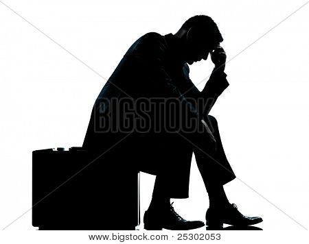 one caucasian business man sitting on suitcase tired despair silhouette Full length in studio isolated on white background