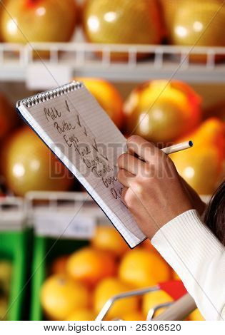 Image of female hands with pen holding product list while buying goods in supermarket