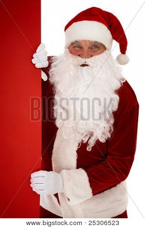 Photo of happy Santa Claus peeking out of red billboard